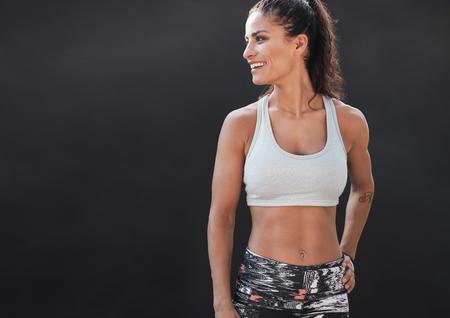 Gelukkige jonge vrouw in sportkleding glimlachend. Gespierd fitness model op een zwarte achtergrond weg te kijken op kopie ruimte. Stockfoto