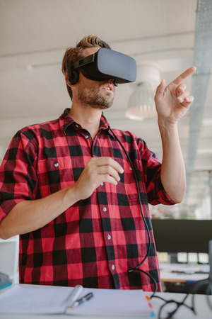 virtual reality simulator: Young man wearing virtual reality glasses and gesturing. Developer using virtual reality simulator headset.
