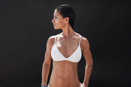 schwarze frau nackt: Studio shot of fitness woman in white lingerie looking away at copy space over black background. Muscular young woman in swimwear.