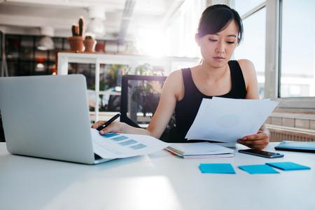 Retrato de la mujer asiática joven que lee documentos en su escritorio. Empresaria en su lugar de trabajo haciendo papeleo. Foto de archivo - 64926234