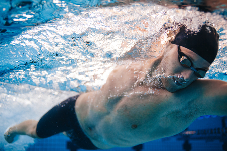 Professional male swimmer inside swimming pool. Underwater shot of fit young man practising in pool.