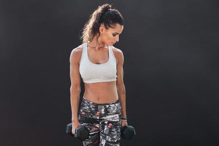 modello di fitness femminile esercizio con manubri. Giovani sollevamento pesi donna per la formazione body building su sfondo nero. donna sollevamento pesi muscolare. Archivio Fotografico
