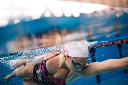 Onderwater schot van vrouw die in pool zwemt. Jong wijfje dat de voorzijde zwemt die in een pool kruipt. Stockfoto