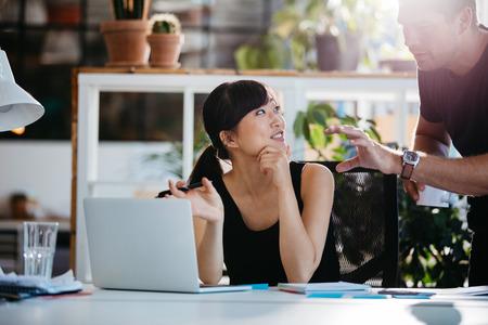 그녀의 책상에 앉아있는 동안 파트너와 이야기 사업가 웃고. 노트북에 프로젝트의 아이디어를 논의하는 전문 직원.
