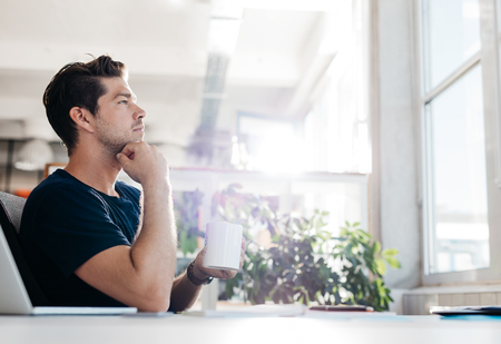 Side view shot of young businessman with coffee in hand sitting at his desk. Man sitting in office and thinking.
