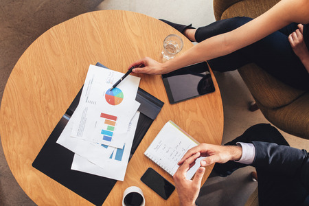 Top view of two business people working with charts around table. Businessman and woman going through business projections while sitting at office lobby.