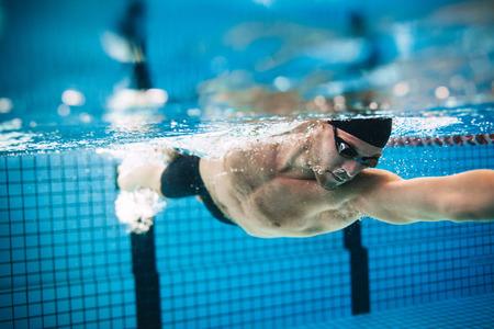 Onderwater schot van professionele mannelijke atleet zwemmen in het zwembad. Man zwemmer in actie.