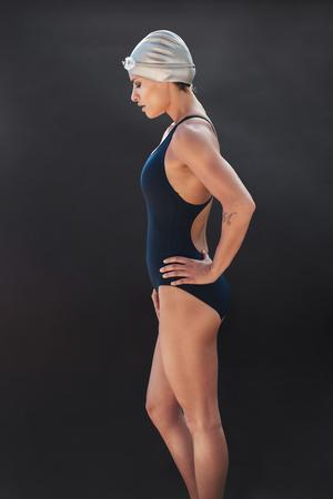 Seitliches Portrait des professionellen weiblichen Schwimmers auf schwarzem Hintergrund. Junge Frau im Badeanzug, der mit ihren Händen auf Hüften steht. Standard-Bild