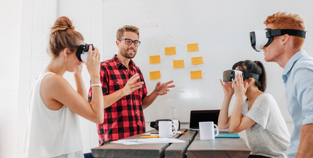 developers: Business people using virtual reality goggles during meeting. Team of developers testing virtual reality headset and discussing new ideas to improve the visual experience.