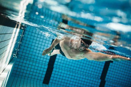 プロの男性スポーツ選手のプールで水泳水中撮影。若い男がプールでクロールを泳ぐします。