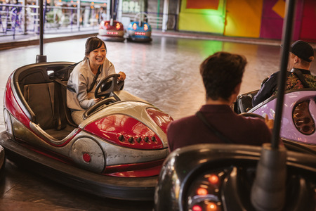 dashing: Friends having fun on bumper car ride in amusement park. Young man and woman having fun with bumper cars at fairground. Stock Photo
