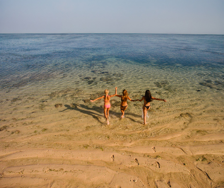 Rear view shot of three young women running into the sea water. Female in swimsuits having fun on beach vacation. Aerial view.