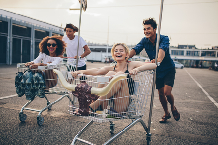 cart road: Young people racing with shopping trolleys on road. Multiracial group of friends racing with shopping cart.