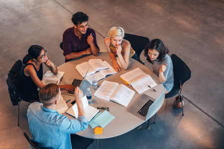 Group of young people studying together. Young students in cooperation with their academic assignment. Stock Photo