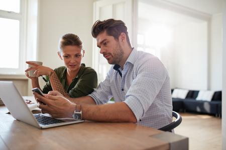 pareja en casa: Tiro de pareja de jóvenes sentados en la mesa con el ordenador portátil en busca de telefonía móvil. Hombre joven y mujer en el hogar con teléfono inteligente. Foto de archivo