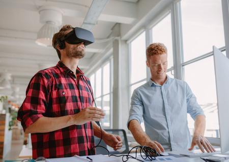 젊은 개발자 노트북 및 가상 현실 안경에서 작동합니다. 사무실에서 가상 현실 안경을 개선하는 두 남자.