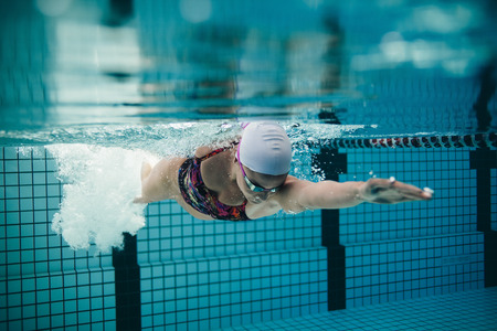 Underwater shot of female athlete swimming in pool. Young woman swimming the front crawl in a pool. Stok Fotoğraf