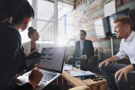 동료와 회의에 앉아 동안 랩톱에서 작업하는 사업가. 회의실에서 비즈니스 사람들입니다.