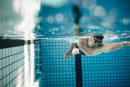 Fit jonge mannelijke zwemmer training in het zwembad. Pro mannelijke zwemmer in actie binnen zwembad.