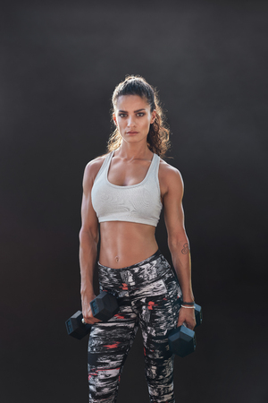 Fitness woman exercising with dumbbells. Beautiful fitness instructor on black background. Female model with muscular fit and slim body.