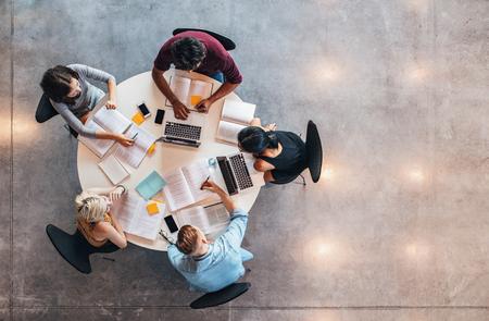 Bovenaanzicht van groep studenten die aan tafel zitten. Universitaire studenten doen groepsstudie. Stockfoto