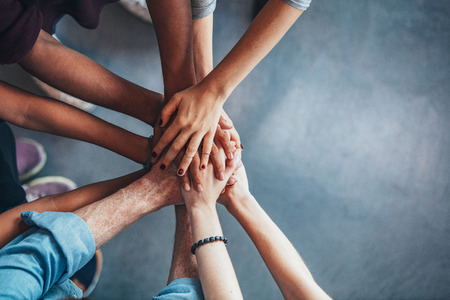 Close up top view of young people putting their hands together. Friends with stack of hands showing unity and teamwork. Stock Photo