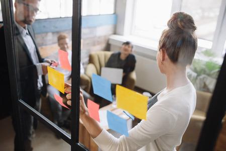 ビジネスマンのオフィスで会議を持ちます。ガラス壁の前に立っている女性はポストイット ノートと同僚にビジネスのアイデアを説明します。