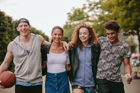 four people: Portrait of multiracial group of people enjoying a walk outdoors. Four young friends walking together and smiling on city street.