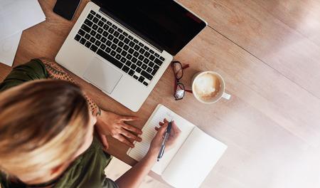 노트북 노트북 및 커피 쓰기 테이블에 앉아 여자의 상위 뷰 촬영. 여성 결정은 일기에 목록을 할 수 있습니다.