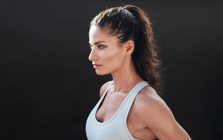 healthy looking: Close up shot of attractive young woman in sportswear posing on black background. Healthy female model looking focused in studio.