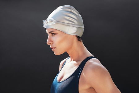 Determined young female swimmer standing against black background. Fit young woman in swimwear. Stock Photo