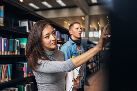 finding: Shot of young female student selecting book from library shelf with man in background. University students taking book from shelf in library.