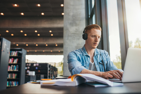 man studying: Young male student with headphones studying on the laptop. Handsome caucasian man sitting at the desk and working on laptop at public library. Stock Photo