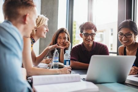 Universitaire studenten die samen aan tafel zitten met boeken en laptop. Gelukkige jonge mensen doen groepsstudie in de bibliotheek.