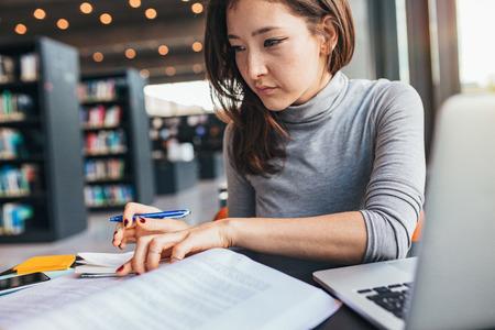 本で勉強し、図書館の机に座っている間、メモを取って若い女性。アジア女性の学生は期末試験の準備します。