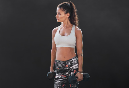 Slim and fit woman lifting hand weights. Muscular female working out with dumbbells on black background. Bodybuilding model doing fitness exercise.