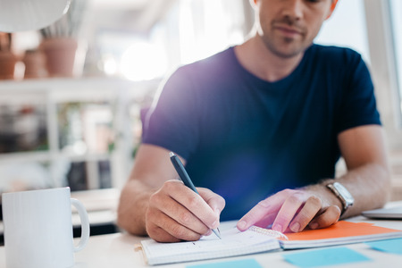 Young businessman writing down important notes in diary at his desk. Young businessman writing in his notepad. Stock Photo