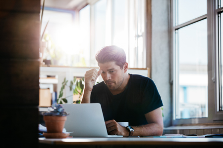 pensando: Joven que trabaja en la computadora portátil en la oficina. hombre de negocios pensando en un problema en su computadora. Foto de archivo