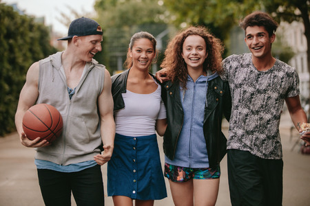 youth group: Portrait of four young friends walking together and smiling. Mixed race group of people enjoying a walk outdoors.
