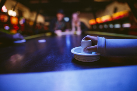 ARCADE GAMES: Young people playing air hockey. Female hand holding striker on table.