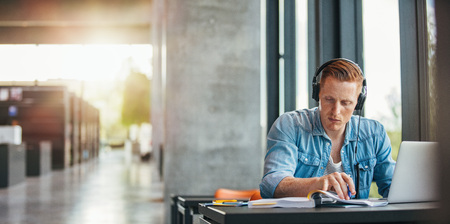 라이브러리 및 독서 책에서 테이블에 앉아 헤드폰을 착용하는 젊은 학생의 초상화. 대학생이 학업을 위해 정보를 찾는 중입니다.
