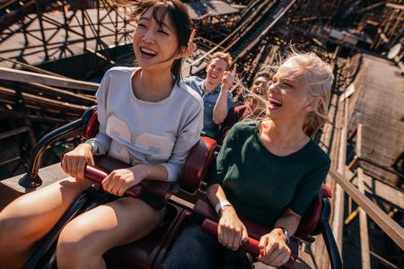 Plan d'un sourire les jeunes chevauchant un roller coaster. Les jeunes femmes et les hommes ayant du plaisir sur le tour du parc d'attractions.