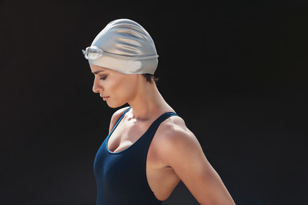 Side portrait of professional female swimmer standing on black background. Young woman in swimsuit and cap. Stock Photo