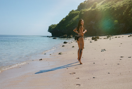 mujeres corriendo: Full length shot of young woman in bikini running on the sea shore and looking back. Beautiful female model enjoying holidays on the tropical beach. Foto de archivo