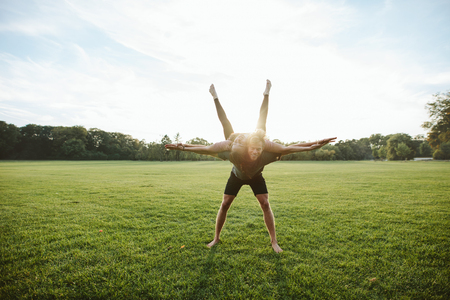 Healthy young couple doing acrobatic yoga workout in park. Man carrying and balancing woman on his back with their hands outstretched.