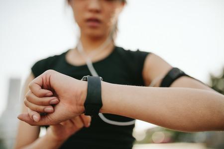 Close up Schuss von junge Sportlerin Smartwatch mit ihrem Trainingsleistung zu verfolgen. Fitness Frau, die ihre Fortschritte auf Smartwatch überwacht.