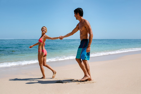 pulling beautiful: Full length shot of romantic couple walking on beautiful tropical beach. Happy young man and woman going into the sea, with woman pulling the man. Stock Photo