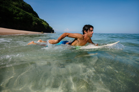 male surfer: Side view shot of young man water surfing in ocean. Male surfer in the sea water with surf board. Stock Photo