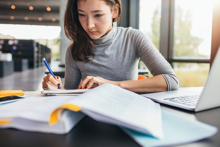 assignments: Close up image of a young female student doing assignments in library. Asian woman taking notes from textbook. Stock Photo