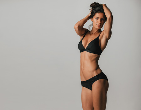 Sexy shapely young woman with a healthy toned body posing in black lingerie with her arms raised to her long hair, three quarter over grey with copy space